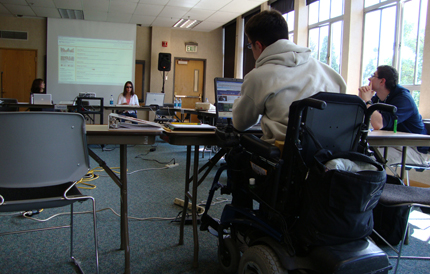 Student in a wheelchair uses a laptop during class.
