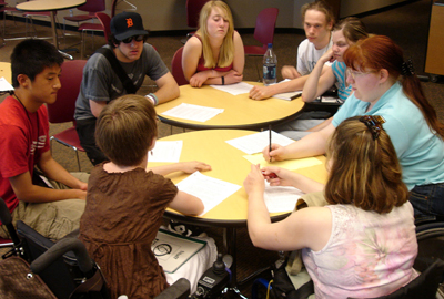 A group of students with disabilities sits around a table