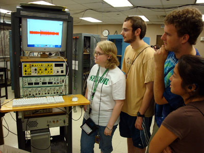 A group of students watches with interest as they gather around a rack of scientific equipment.