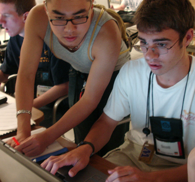 A student helps a peer use a computer