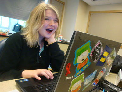 A student using a computer smiles