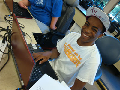 Male student with cap smiles while working on a laptop.