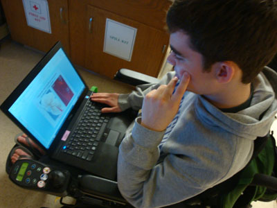 A student sitting in a wheelchair uses a laptop