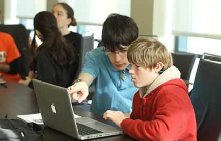 A student who is hearing impaired works on a computer project with another student.