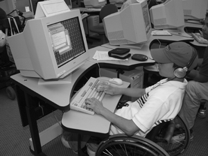 Photo of a student in a wheelchair using a computer at an adjustable table.