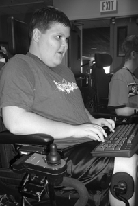 Photo of student with a mobility impairment using a computer.