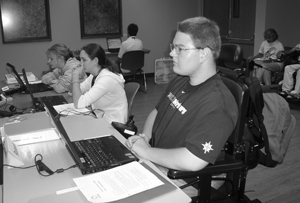 Photo of a student in a wheelchair seated at a computer listening to a lecture.