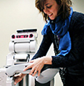An Engineering professor positions a robot during a demonstration