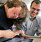 A mentor works with a student on a computing project