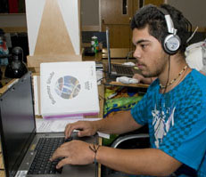 Photo of a student at a computer listening to headphones.