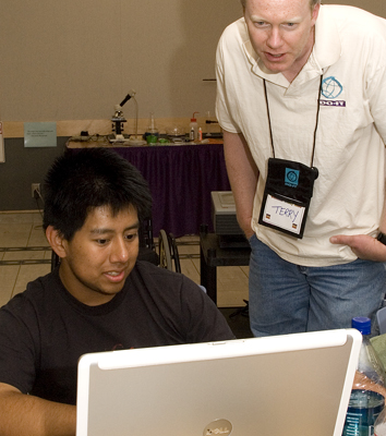 Photo of student and instructor working on laptop.