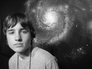 Photo of student in front of large picture of a spiral galaxy