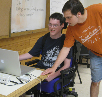 Picture of a Courage Camper in a wheelchair working on a laptop while the instructor observes.