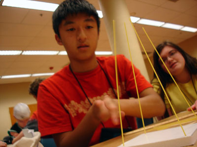 Picture of two students designing a structure using dried spaghetti.