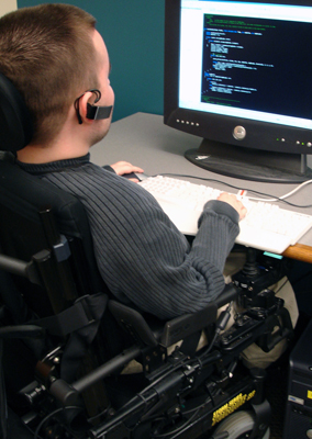 A student in a wheelchair uses assistive technology to access a computer