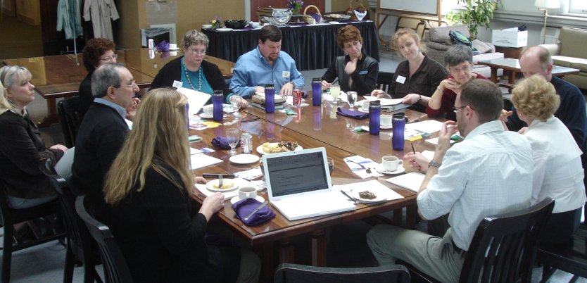 Photo of Think Tank: Serving Veterans with Disabilities participants gathered around a conference table in discussion